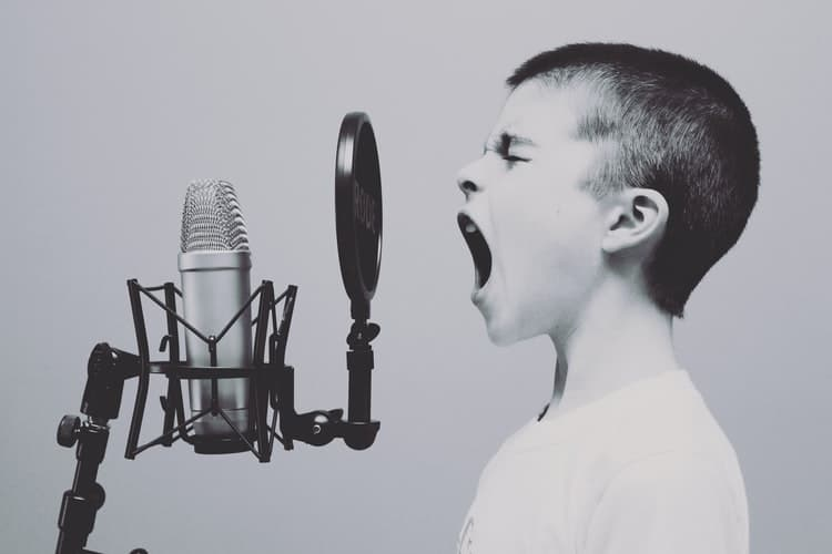 photo of a boy shouting into a microphone