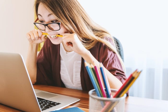 Girl biting pencil in frustration at laptop