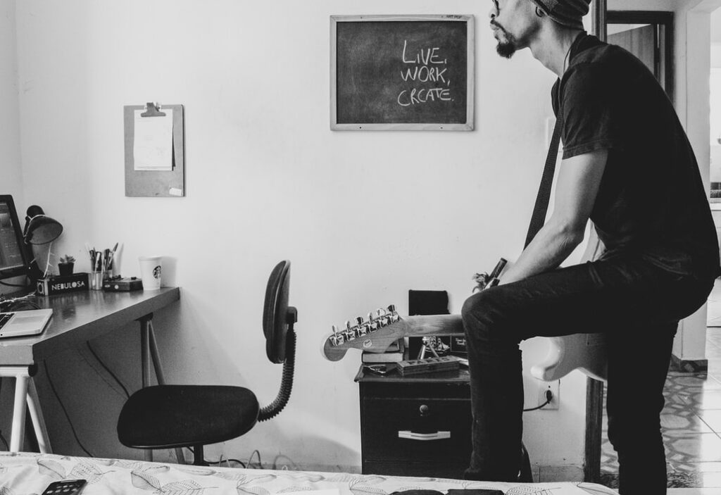 Black-and-white photo of a musician at home playing the guitar