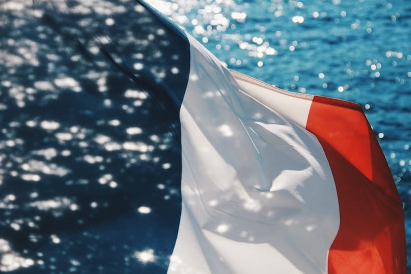Photo of French flag waving in the wind, with the ocean in the background
