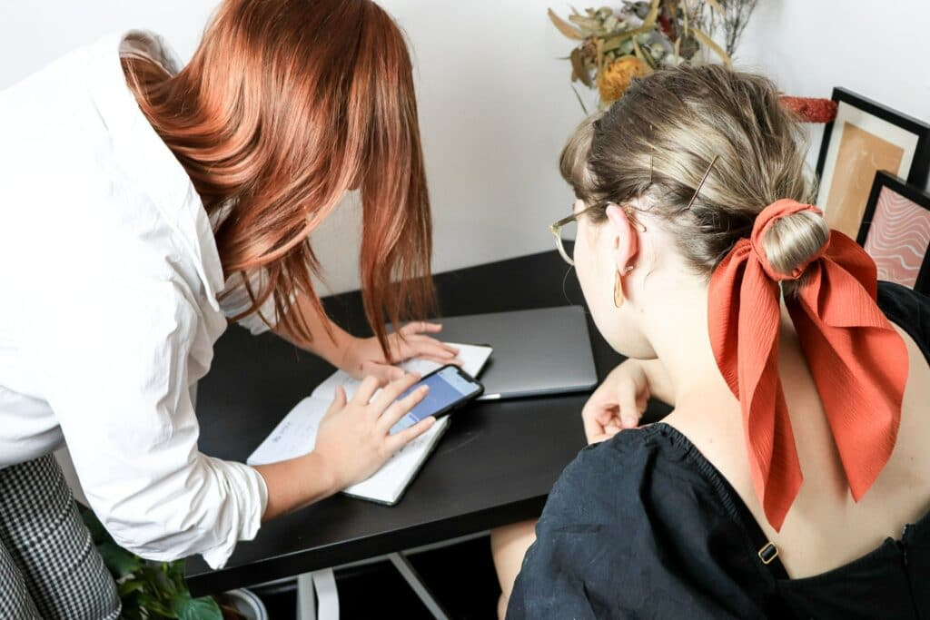 Two local community managers looking at their phones together at a desk