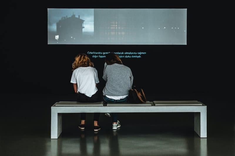 image of two women sitting in a museum while watching a video with subtitles